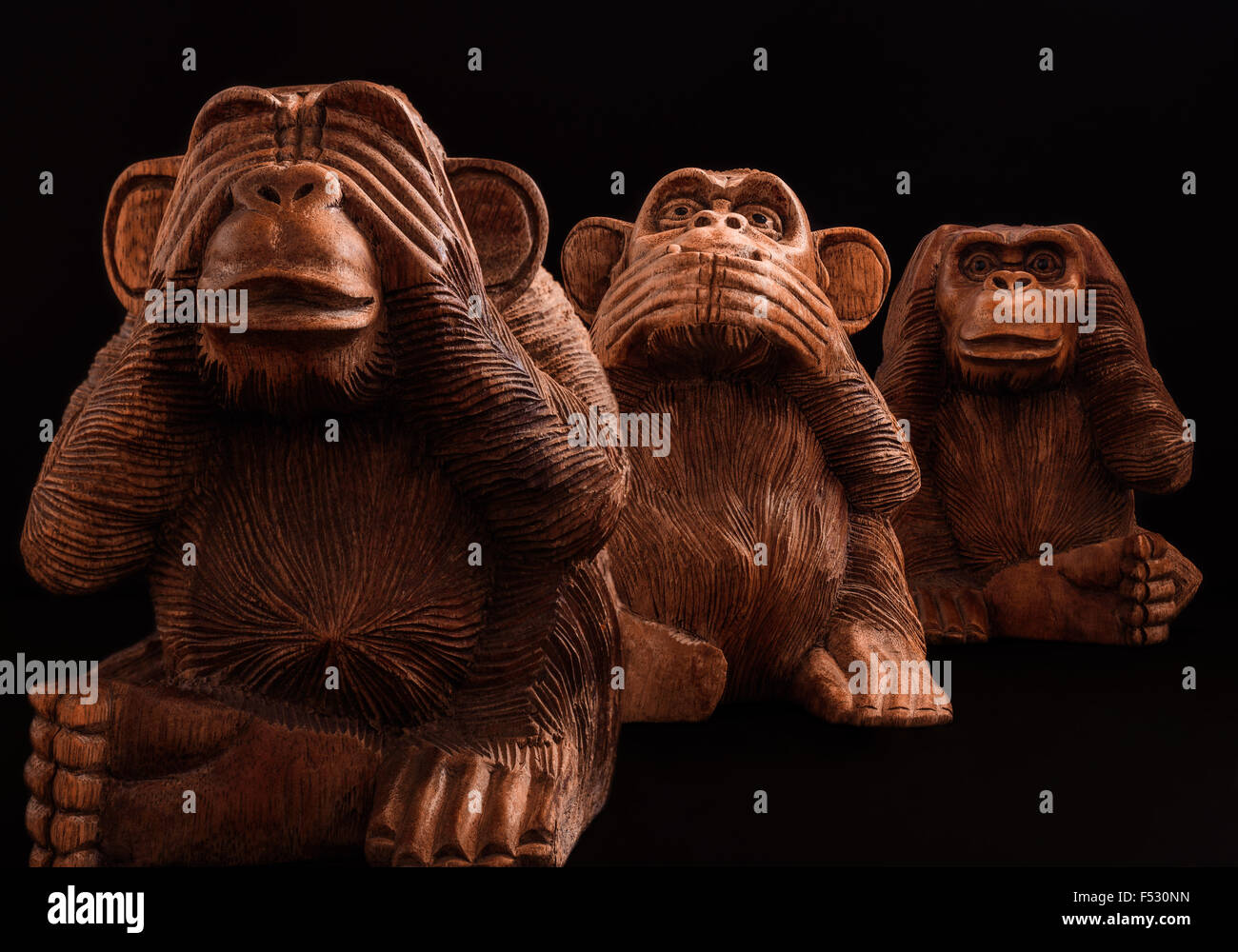 Three wise monkeys wooden ornaments - Three Wise Monkeys Figurines Of Wood On A Black Background Stock Image