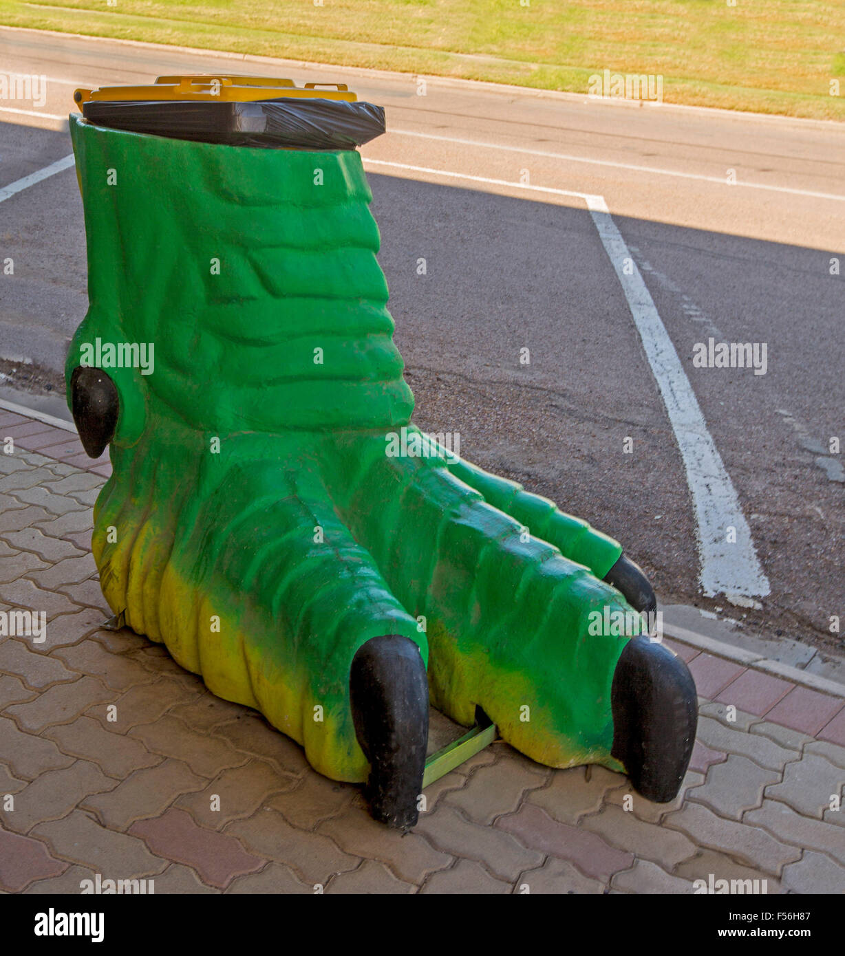 stock photo unique rubbish garbage bin replica of green dinosaur foot on paved footpath in outback australian town of winton