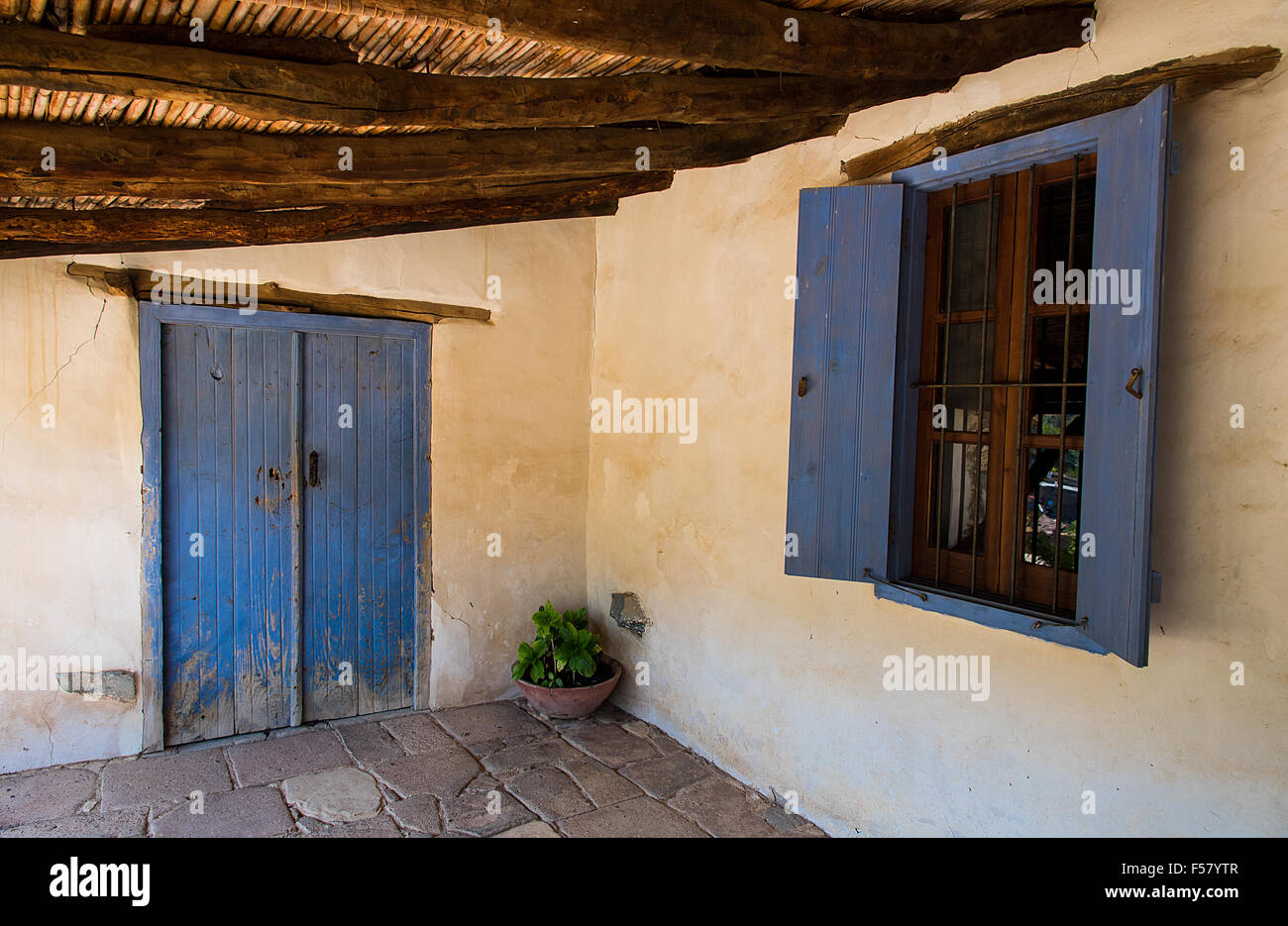 Veranda of an old traditional cypriod house with blue wooden door and windows yellow wall and a wooden roof at the Village of F & Veranda of an old traditional cypriod house with blue wooden door ...