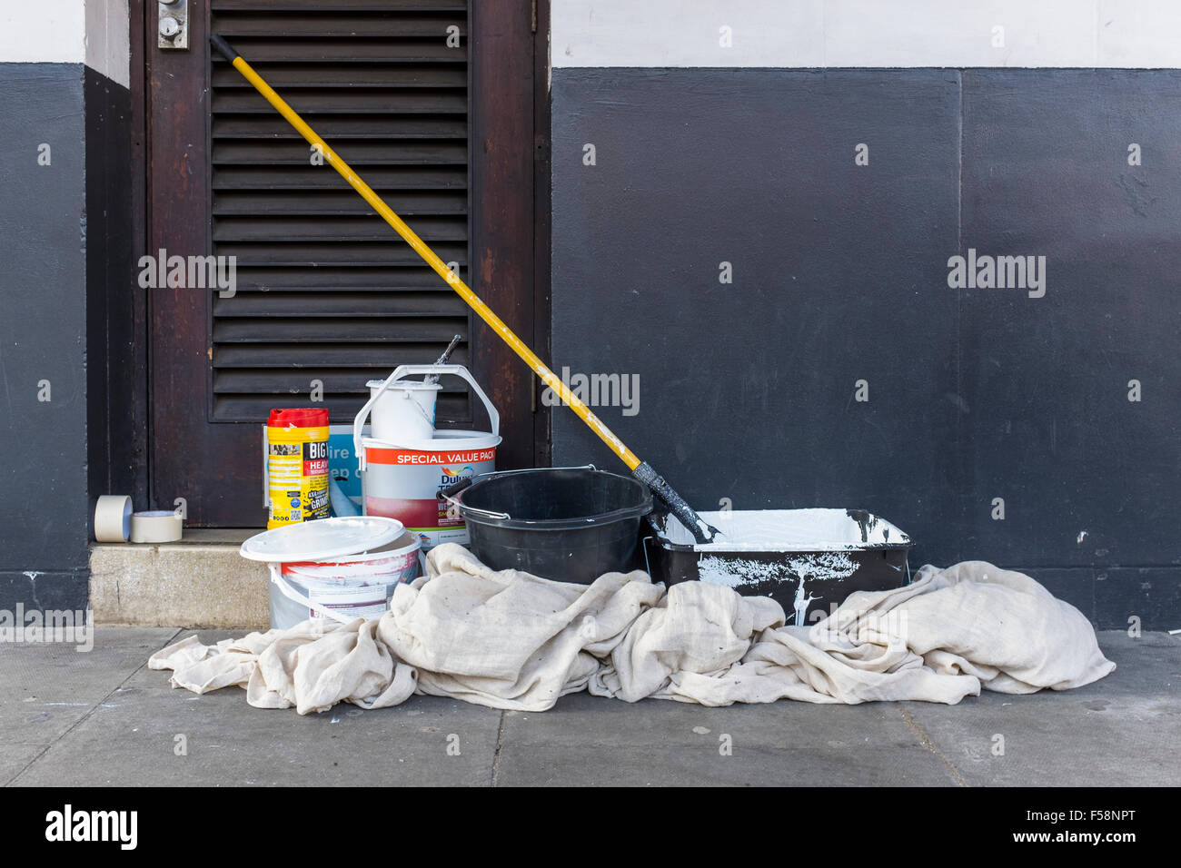 White Paint Pots And A Large Paint Roller All Standing On A Paint Sheet  Next To An Outside Wall On The Pavement In The Street