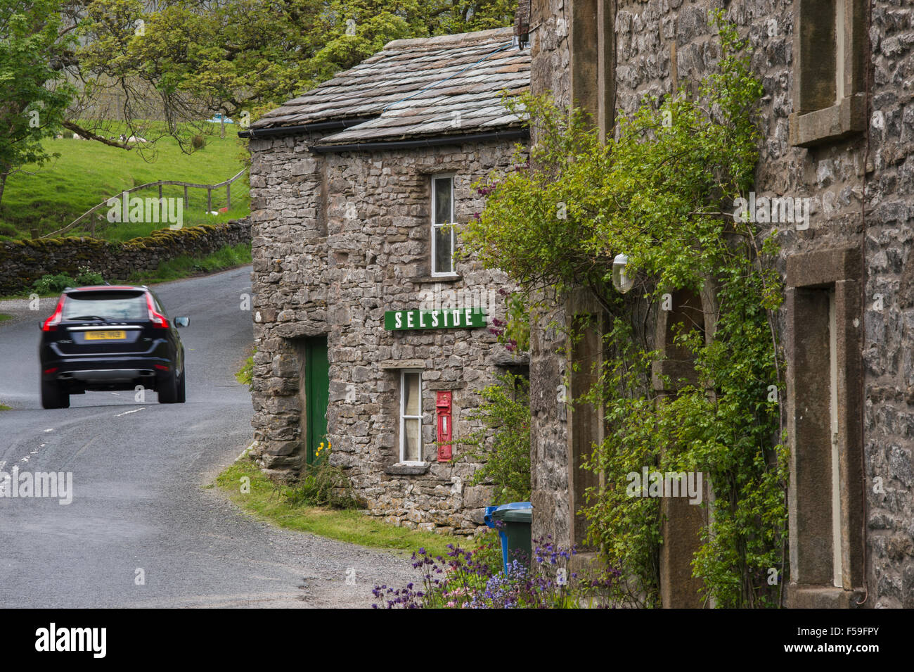 Car Passes Traditional Stonebuilt Roadside Cottages Name Sign - Car sign and name