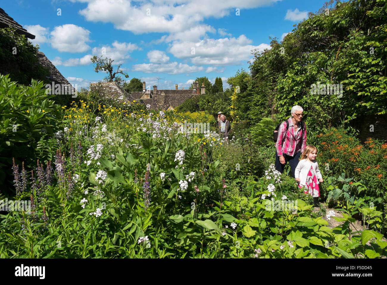People walking up the path of a beautiful garden in the Open