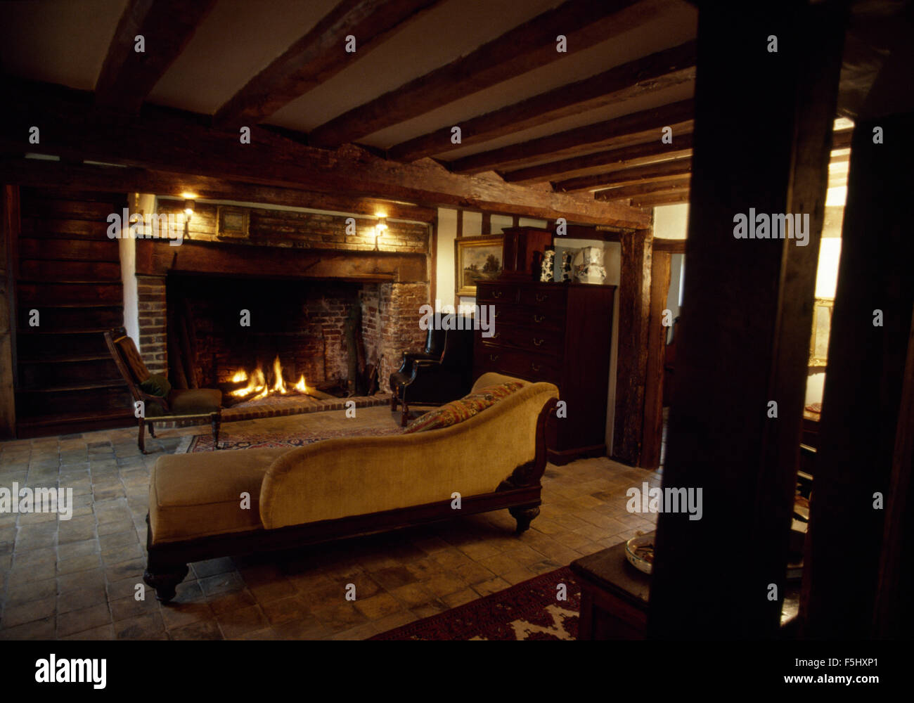 Velvet chaise longue in old fashioned living room with inglenook ...