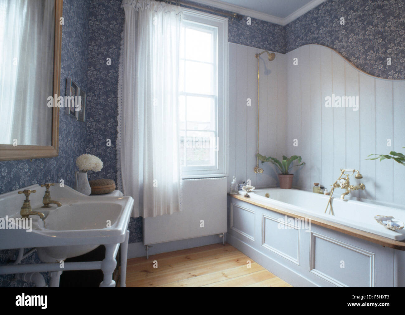 Tongue and groove for bathrooms - White Tongue Groove Panelling Above Bath In Seventies Bathroom With Blue Floral Wallpaper Stock