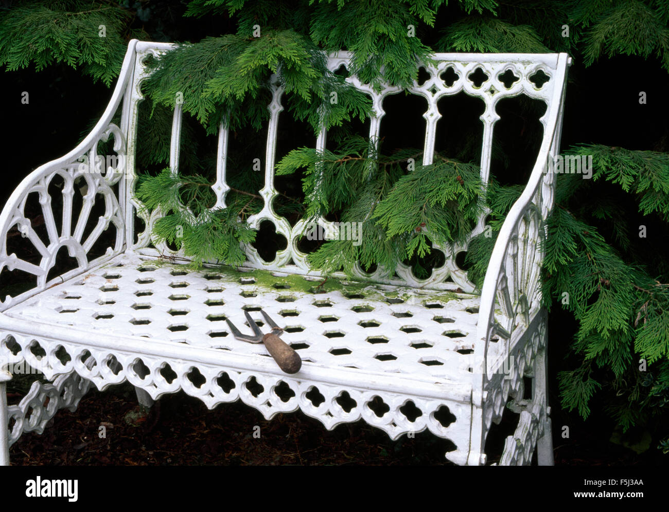 Small Garden Fork On A White Wrought Iron Garden Bench In Front Of A Green  Conifer Shrub