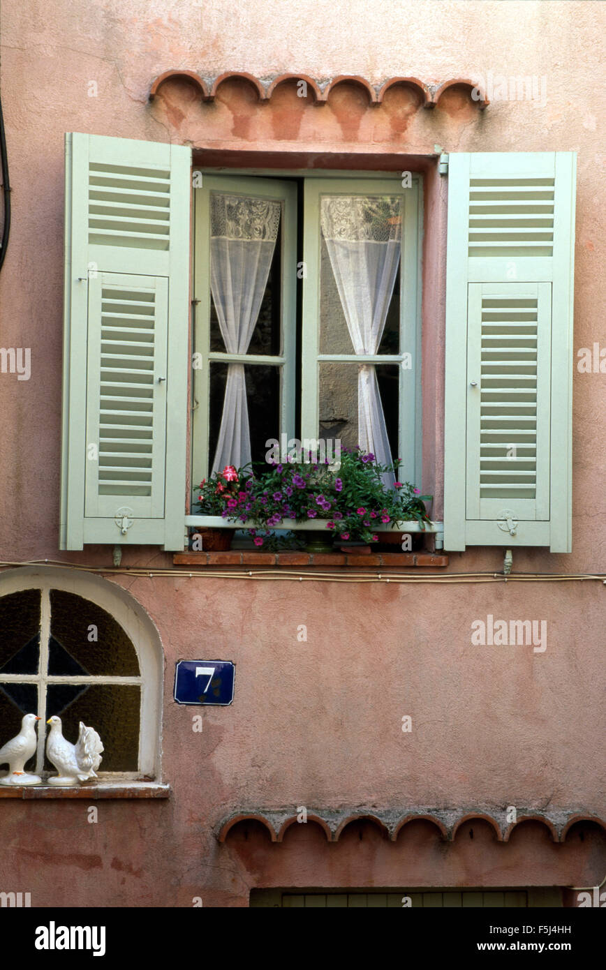 French cottage exterior - Exterior Of A Pink French Cottage With Pale Green Shutters On A Window With Lace Curtains