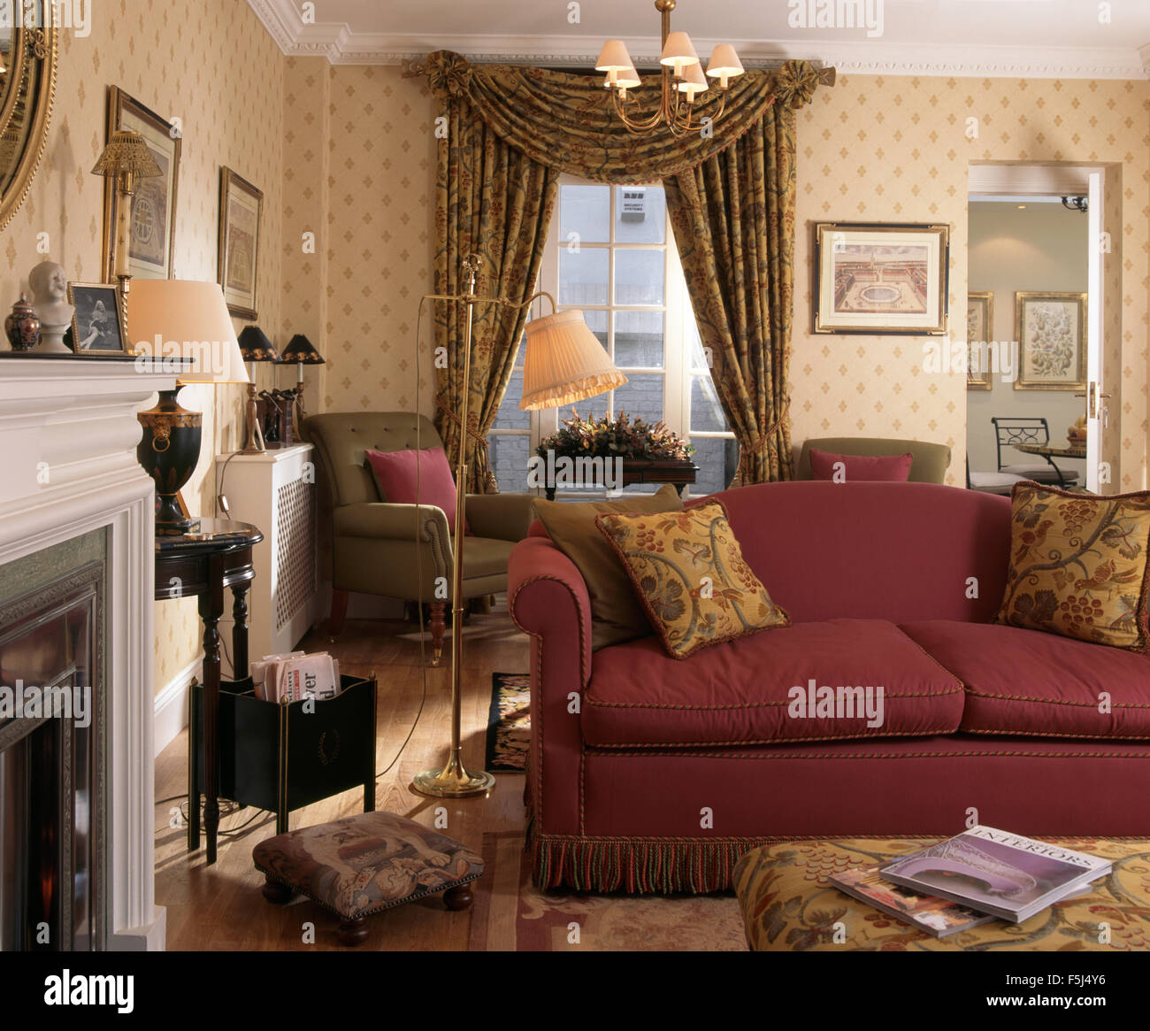 Red patterned curtains living room - Red Sofa In An Old Fashioned Nineties Living Room With Swagged Curtains And Patterned Wallpaper
