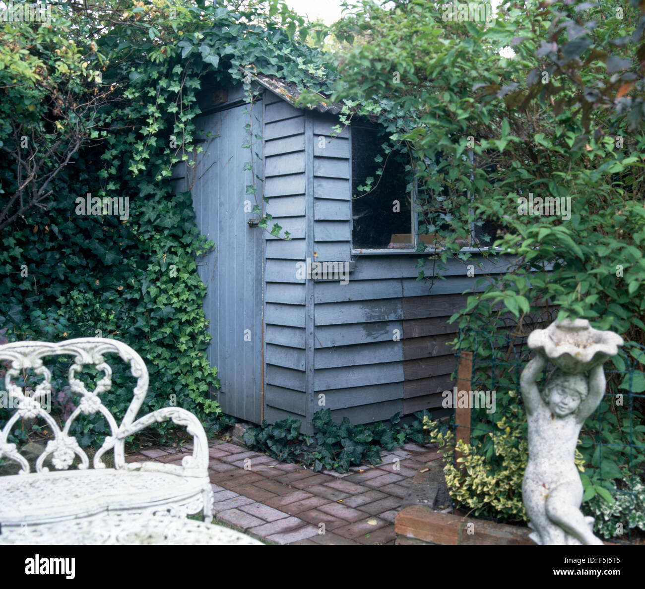 Stock Photo   Stone Statue On Patio With A White Wrought Iron Seat And A  Small Blue Painted Shed Covered With Ivy