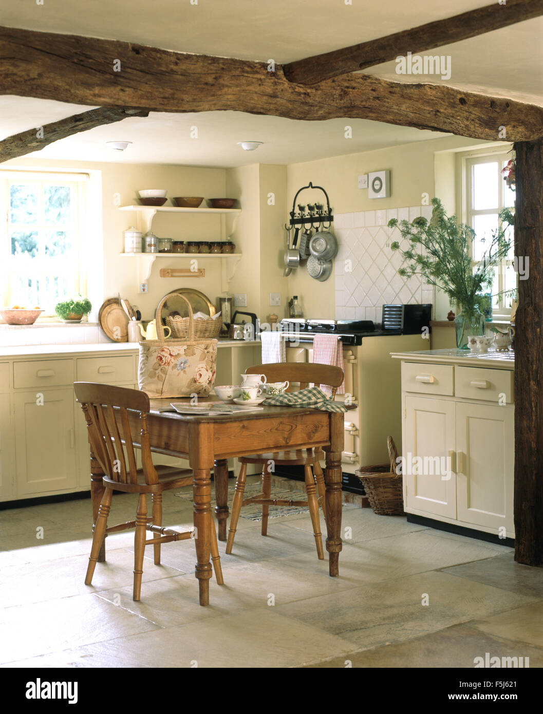 Stock Photo   Vintage Pine Dining Table And Chairs In A Cream Cottage  Kitchen With A Cream Range Oven And Rustic Wooden Ceiling Beams