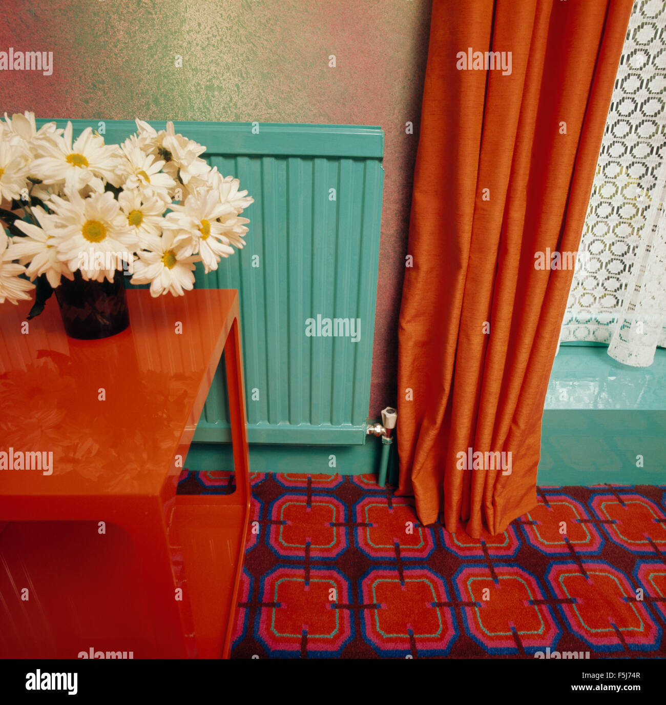 Close Up Of Orange Curtain And Vibrant Patterned Carpet In Seventies Dining Room With A Turquoise Painted Radiator