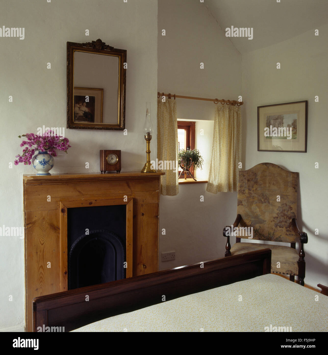 Mirror above a simple pine fireplace in an eighties economy style