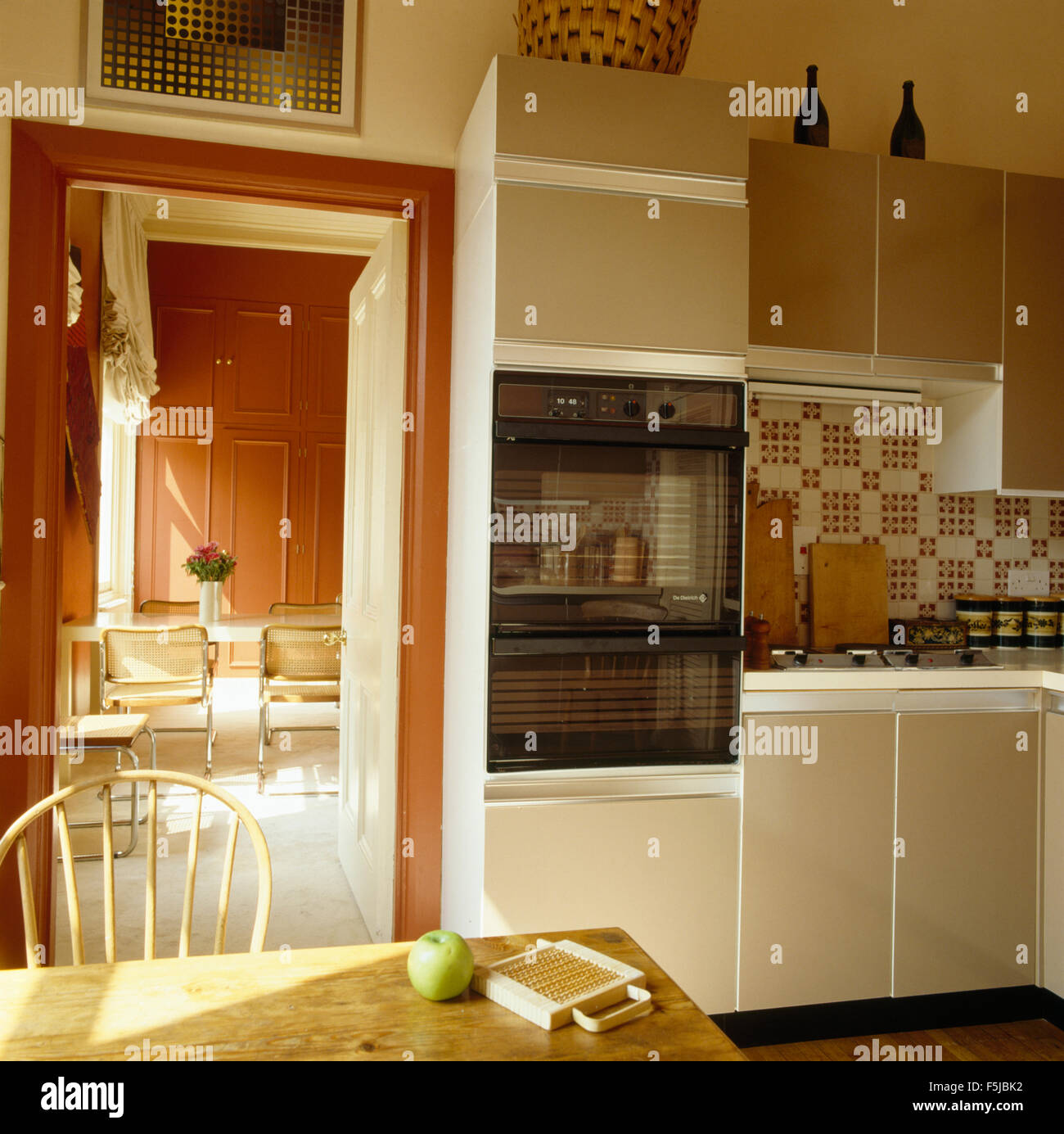 Seventies Kitchen With Fitted Electric Oven Beside Doorway To Terracotta Painted Dining Room