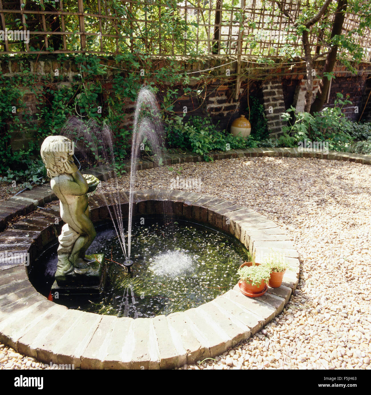 Stone statue of a boy in small circular pool with a for Circular garden ponds