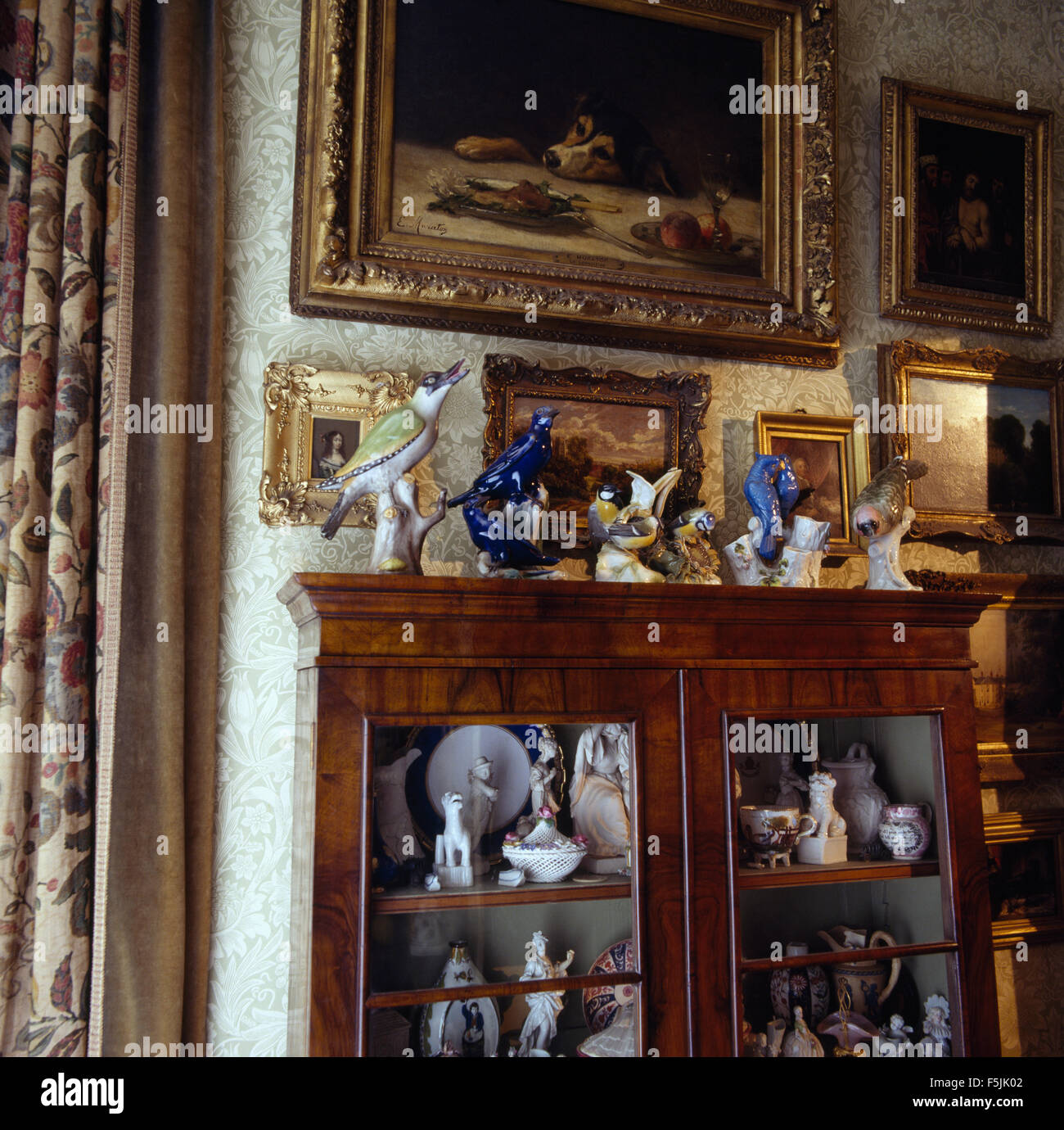 Paintings On Wall Above Antique Glass Front Cabinet With A Collection Of  Antique China Figurines And Ornaments