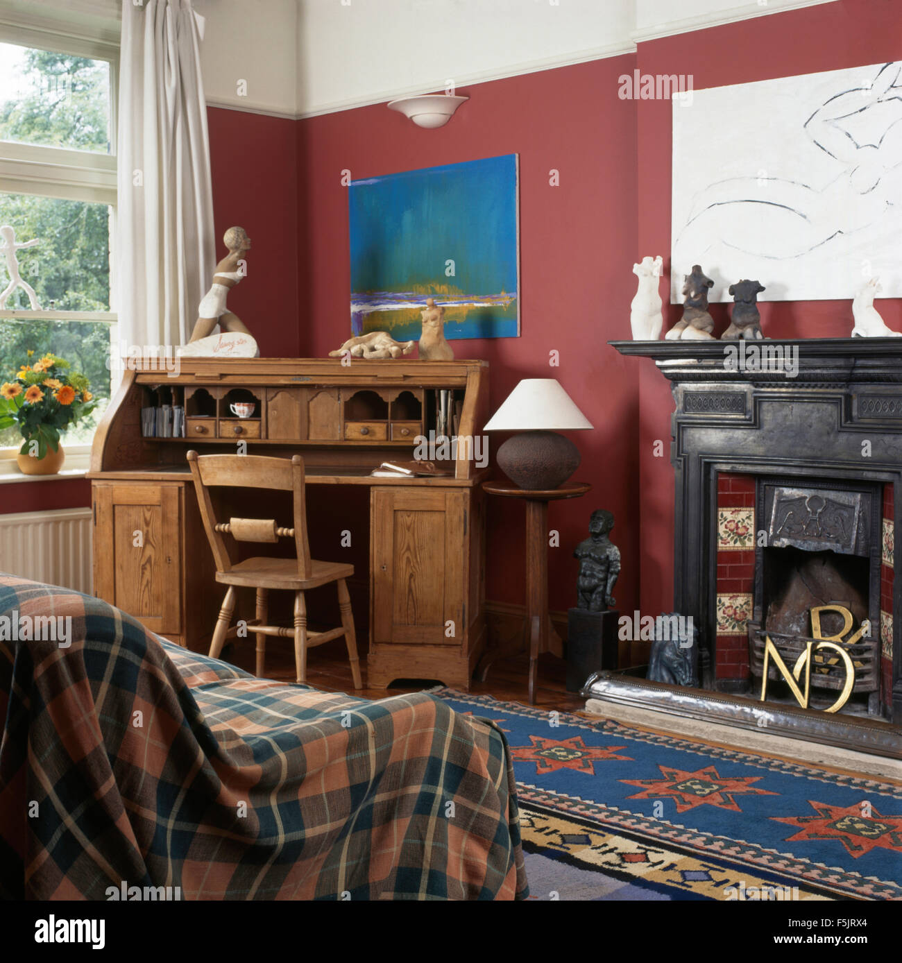 Plaid throw and old pine bureau in a red nineties living room with