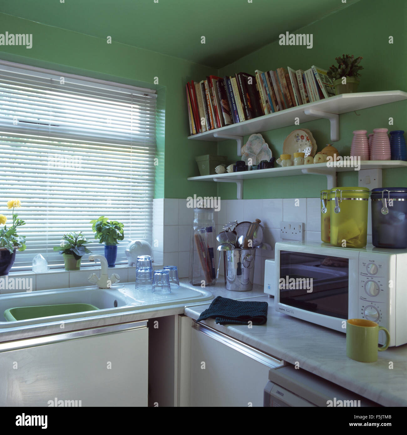 Kitchen shelves for microwave - Open Shelves Above Worktop With Microwave In A Green Economy Style Nineties Kitchen