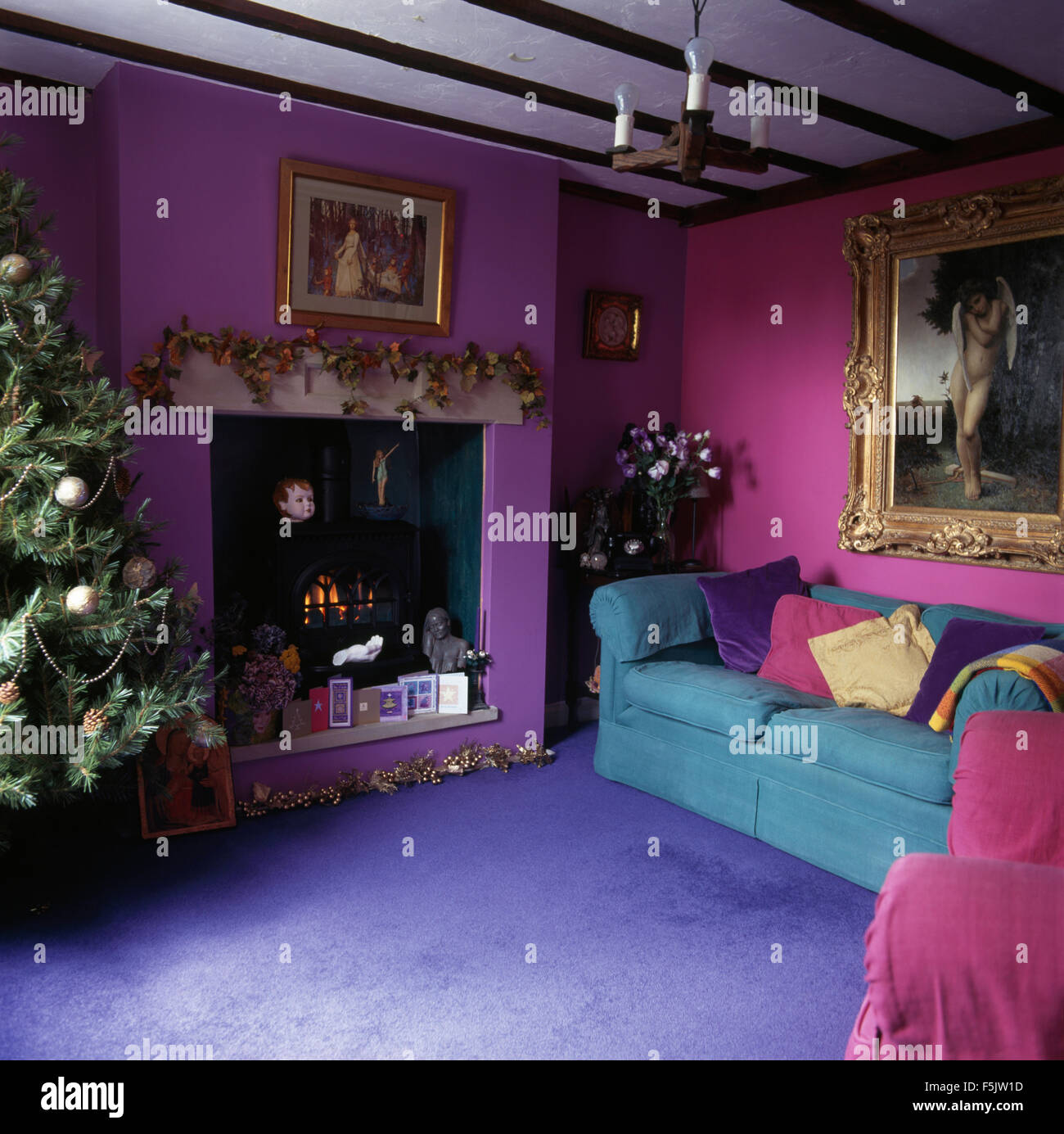 Bright blue carpet and turquoise sofa in purple and pink nineties living room with a decorated christmas tree