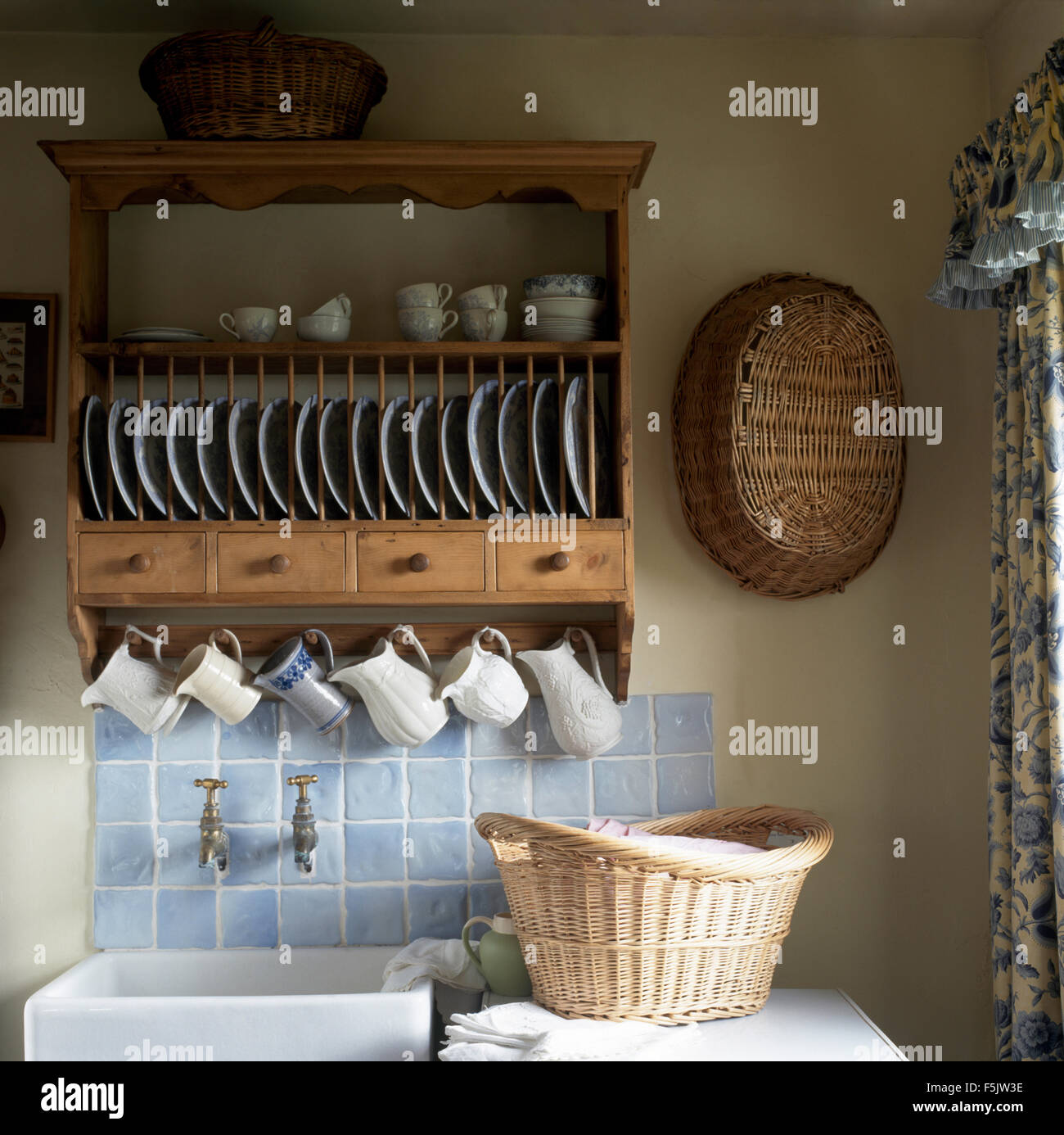 Pine Plate Rack And Row Of Jugs Above Sink In Cottage Kitchen With Laundry  Basket On Worktop