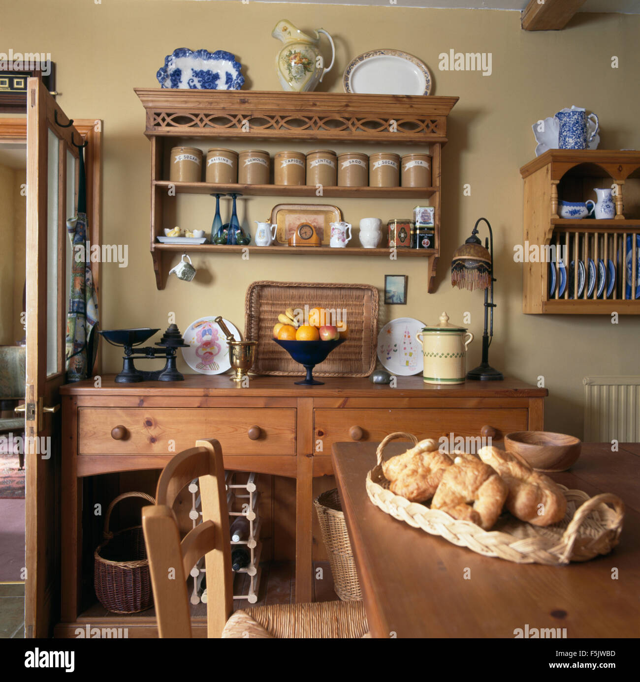 Basket Of Croissants On Table In A Cottage Kitchen Dining Room With Pine Shelves Above Dresser