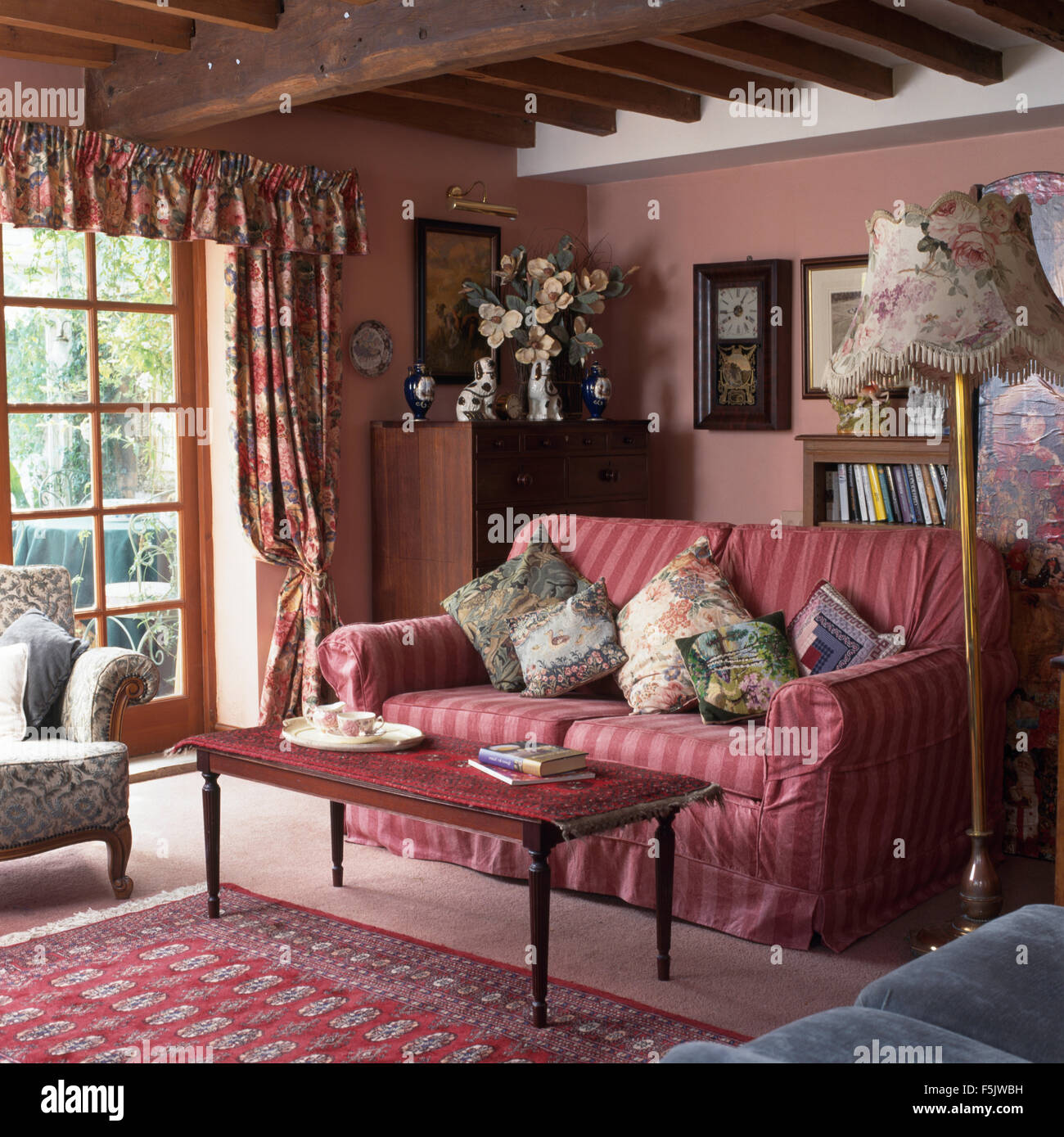 Small rug on coffee table in front of pink striped sofa with Stock ...