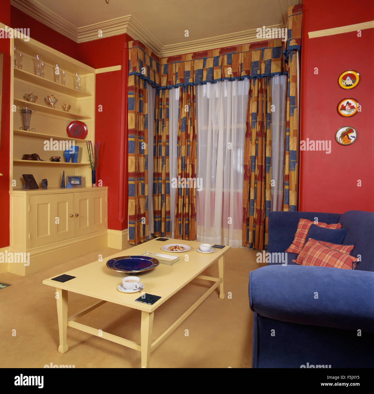 Red patterned curtains living room - Patterned Curtains With Voile Drapes In A Red Economy Style Nineties Living Room With A Blue