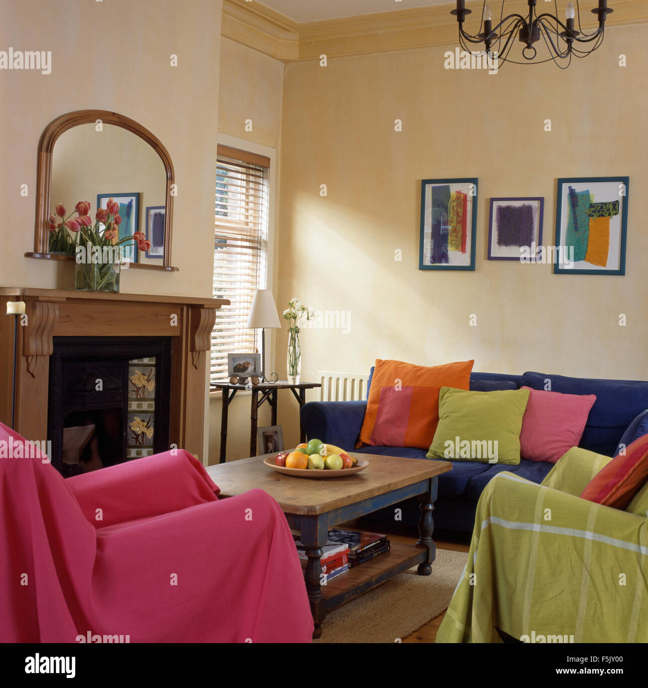 Pink And Lime Green Throws On Chairs In Economy Style Nineties Living Room  With Colorful Cushions On A Blue Sofa