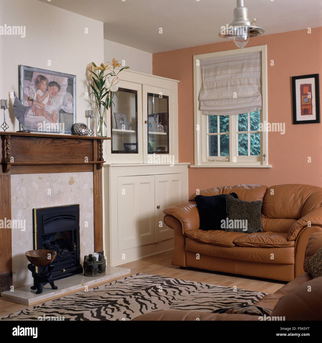 white blind on window above tan leather sofa in pink nineties living room with tiger print