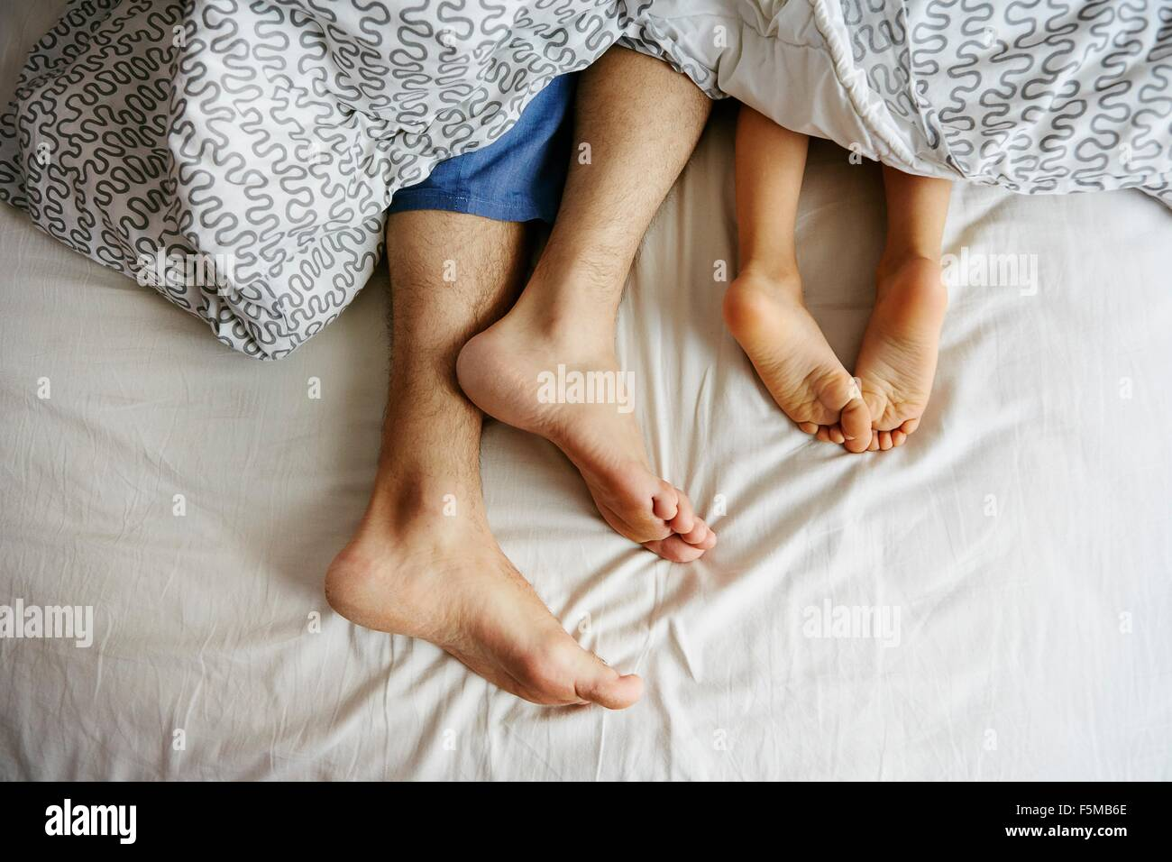 bare feet and legs of father and young son lying in bed