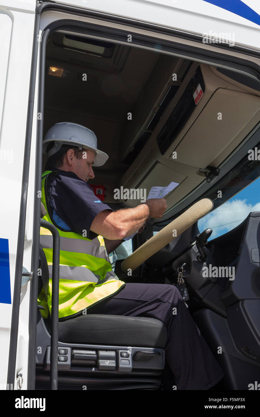 A Lorry Driver In His Cab With The Door Open Checking