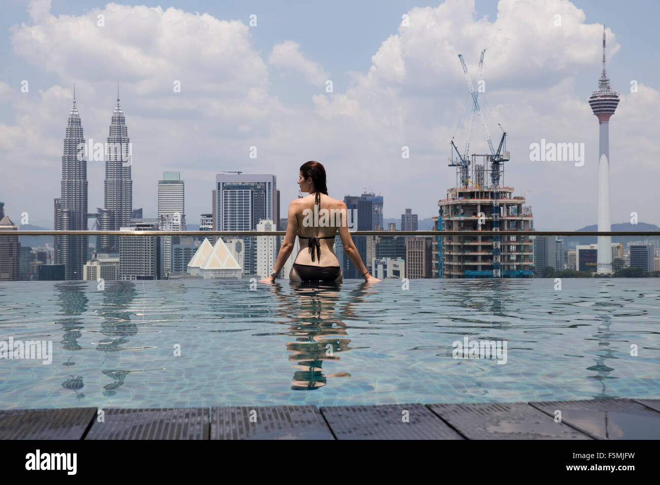 A woman in a luxury rooftop pool in kuala lumpur stock photo royalty free image 89578717 alamy for Best hotel swimming pool in kuala lumpur