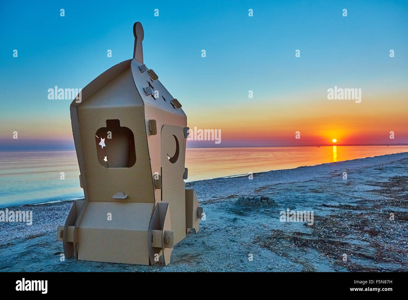 Ecoconcept cardboard toy spaceship at sea coast and sunset. eco concept stock