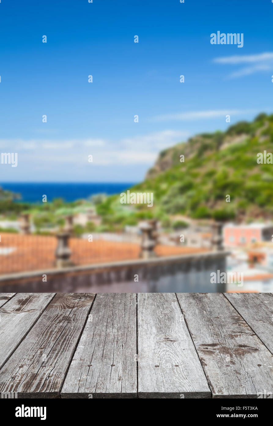 Empty wooden table perspective with blurred bright coastal town
