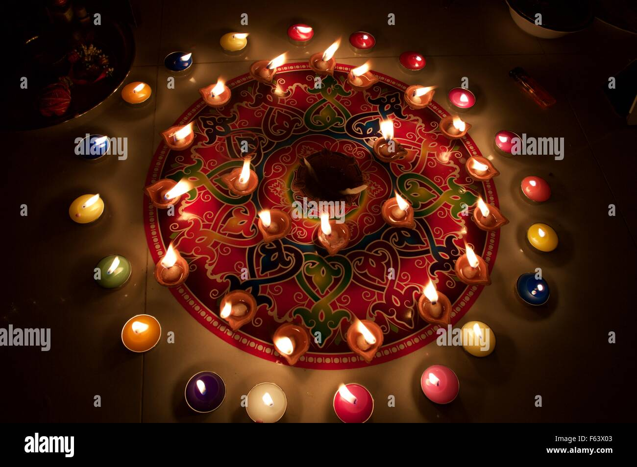 Beautiful rangoli with colorful candle and diyas for ...