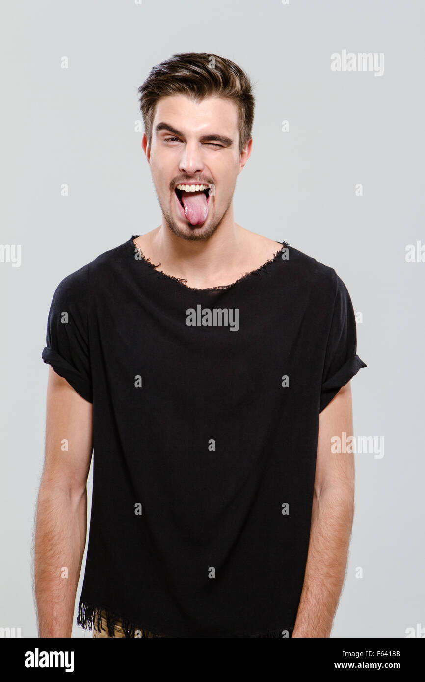 Black t shirt guy - Stock Photo Young Funny Handsome Guy In Black T Shirt Winking And Sticking Out His Tongue