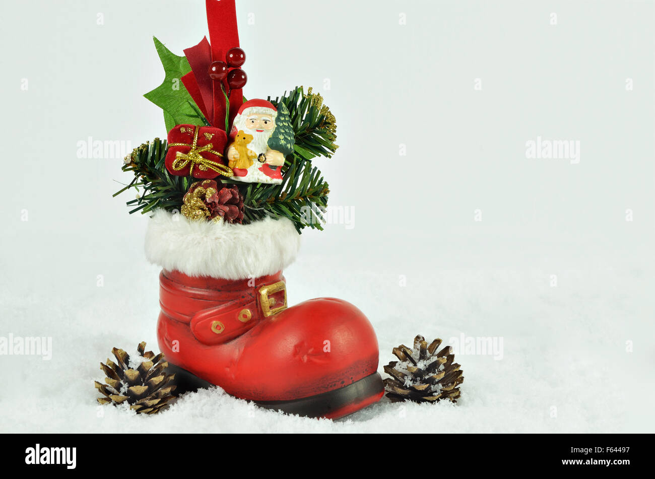 santa claus with fir sprigs inside a red boot with white fur