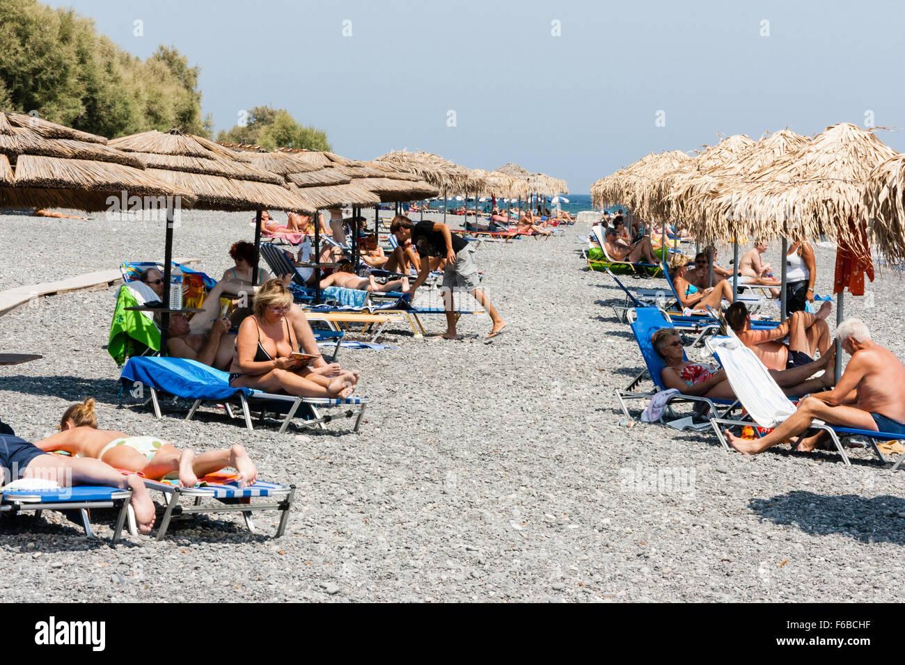Kamari beach with rows of sun recliners and beach parasols sunbathers & Santorini Thira. Kamari beach with rows of sun recliners and ... islam-shia.org