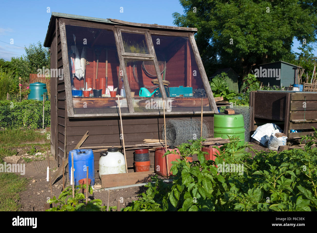 a potting shed garden shed with large open glass front area ready for using to