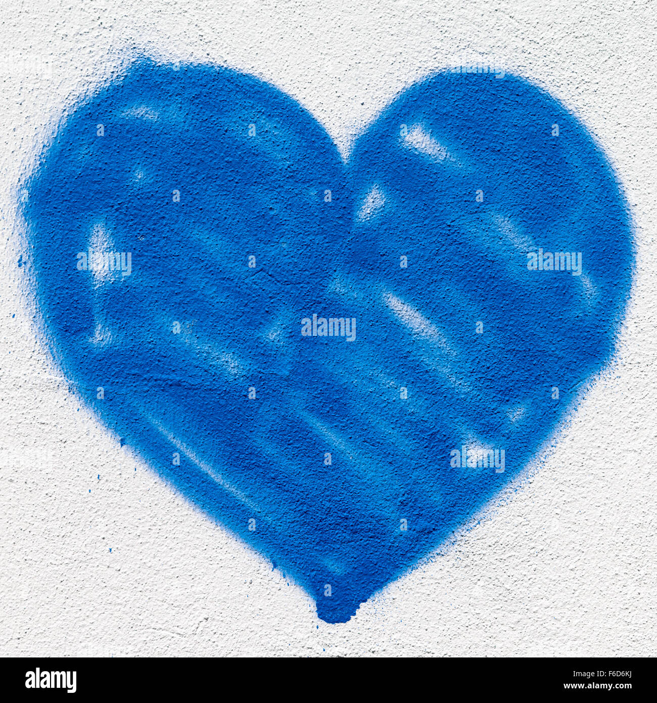 a big blue heart painted on the wall with spray paint