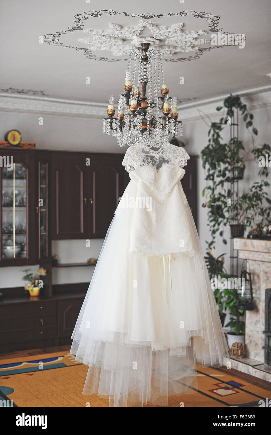 White wedding dress hanging on the chandelier stock photo royalty white wedding dress hanging on the chandelier arubaitofo Images