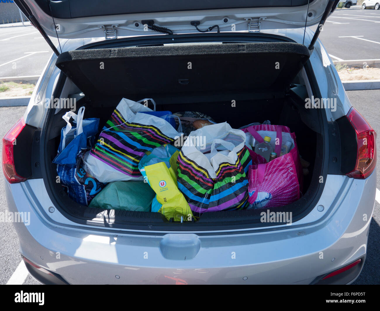 a car boot of colourful plastic shopping bags stock