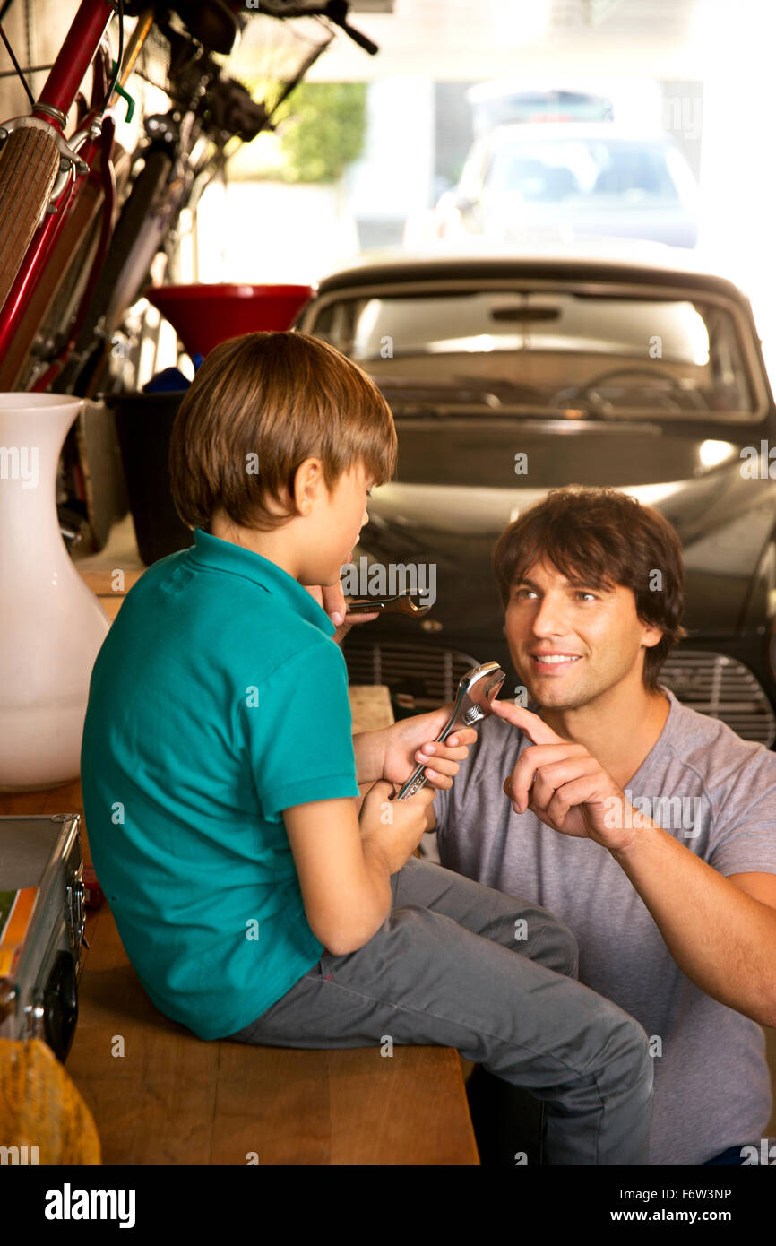 Father and son in garage with vintage car and tools Stock Photo ...