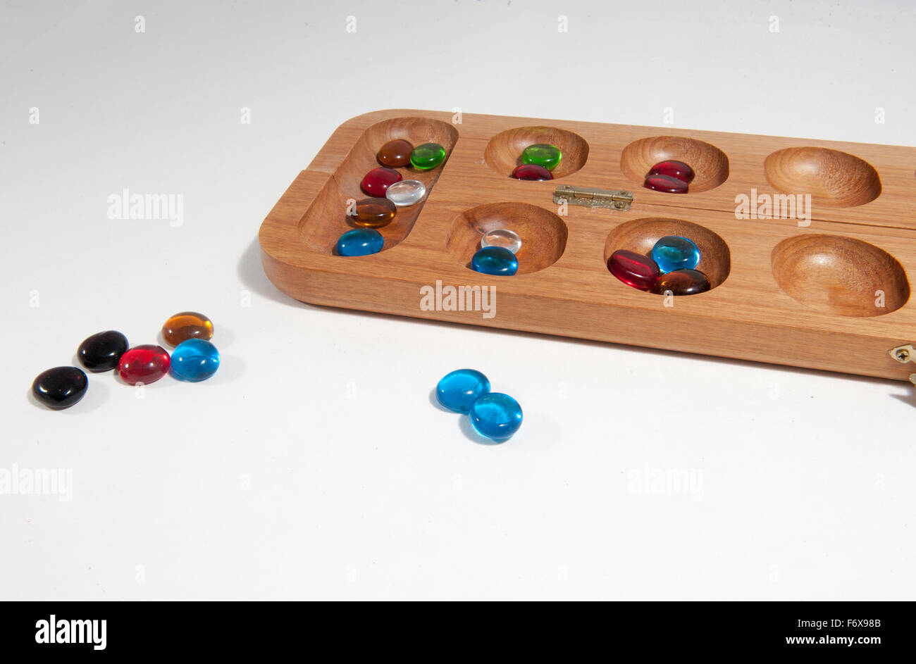 Mandala Board Game And Coloured Glass Stones Against A White Background