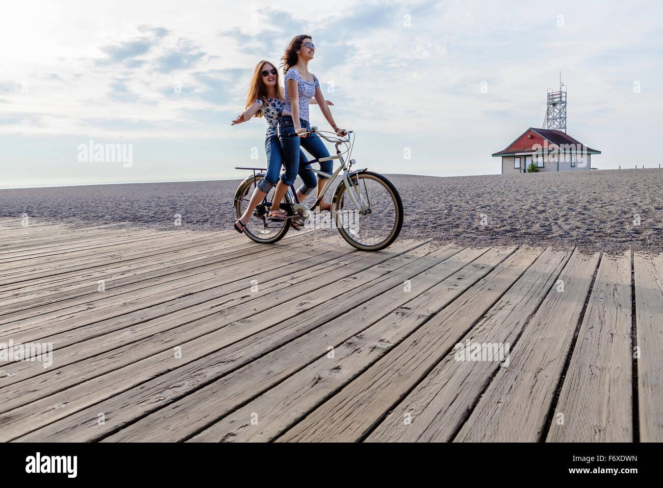 Two Girls Riding Double On A Single Bike On A Beach Boardwalk