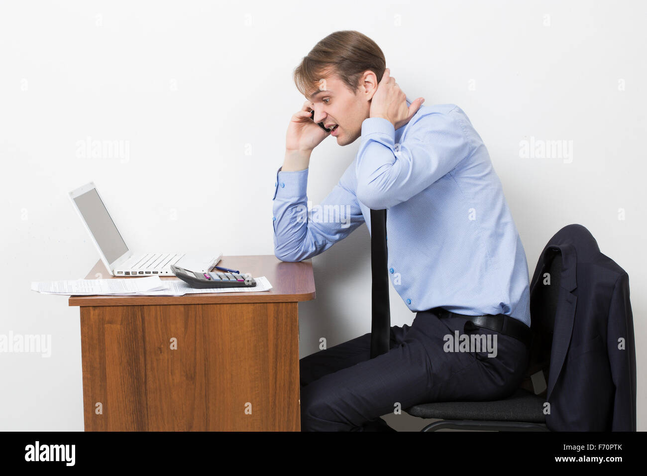 Frustrated office worker on the phone holding stock photo image - Stock Photo Frustrated Office Worker On The Phone Holding Neck