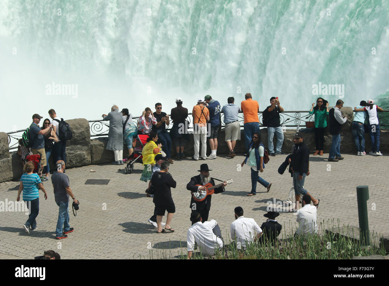 Stock photo tourists viewing the canadian falls horseshoe falls view from niagara falls ontario canada man playing guitar in foreground