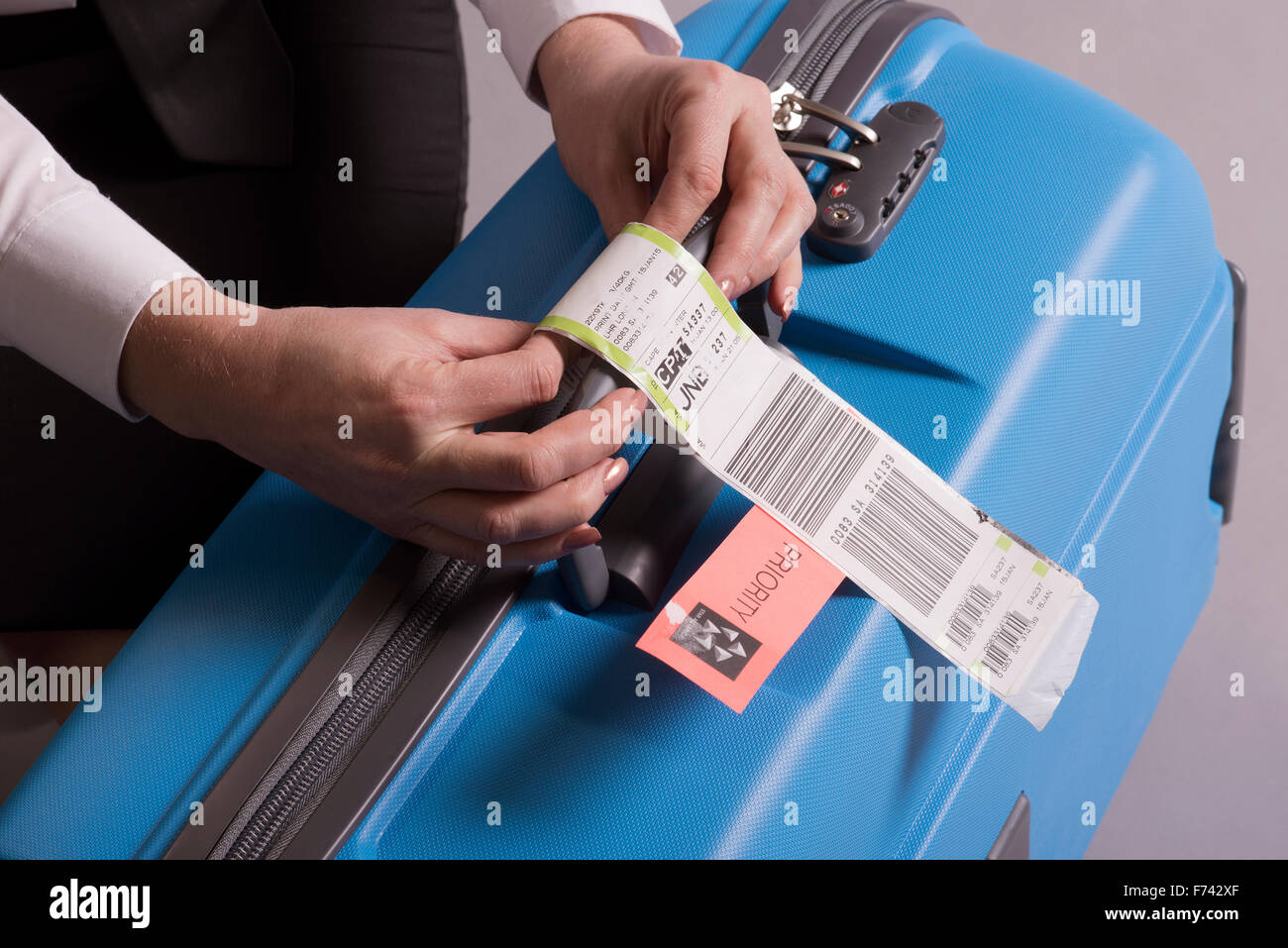 Priority Tag: Airline Check In Luggage Tag Being Attached To A Suitcase