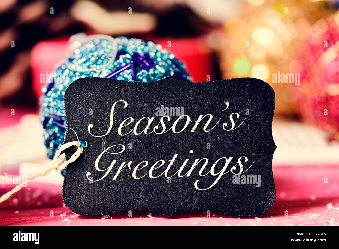 Seasons greetings christmas stock photos seasons greetings closeup of a black label with the text seasons greetings and on a rustic wooden surface kristyandbryce Images