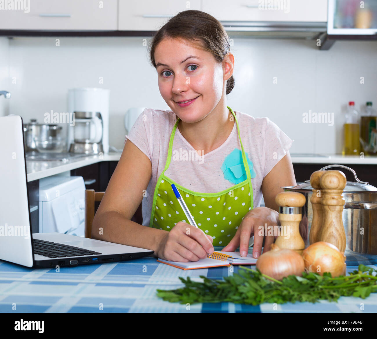 Happy Young Woman Making Shopping List In Domestic Kitchen Stock ...