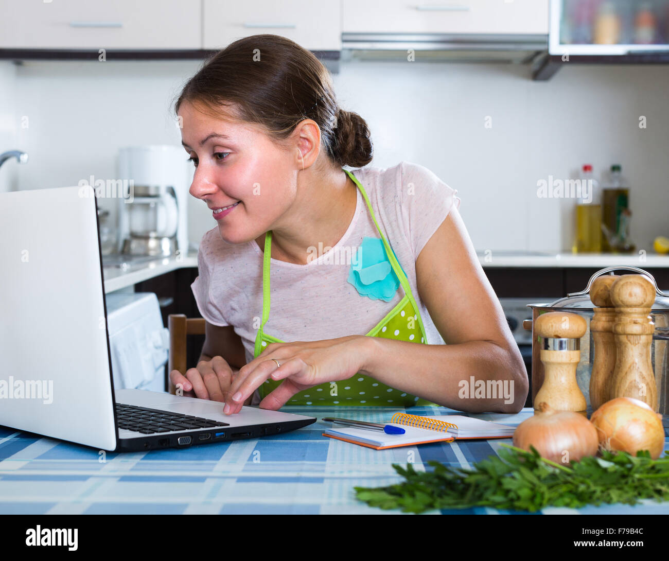 Smiling young housewife making shopping list in domestic kitchen ...