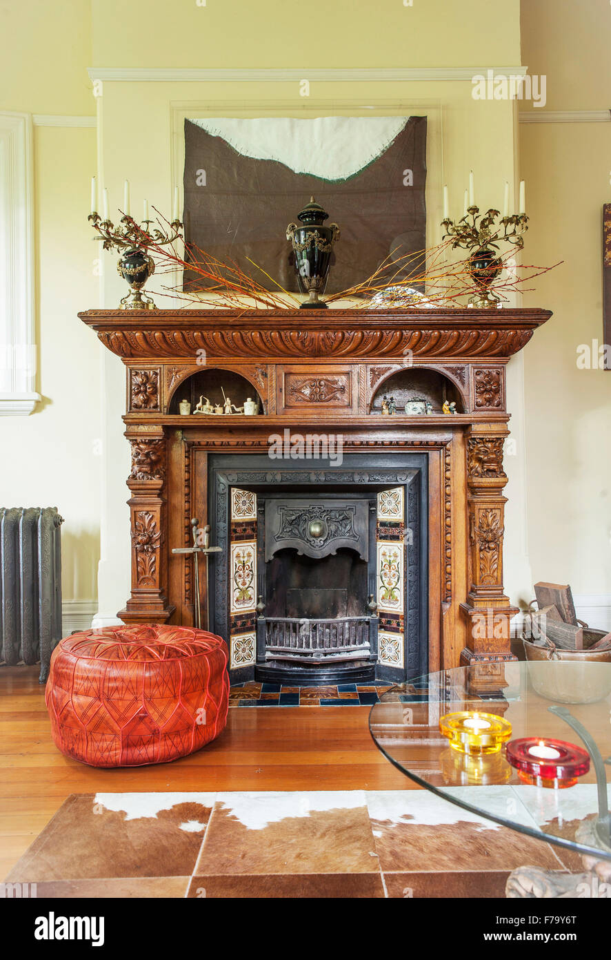 leather pouf by a carved wooden fireplace in home of designer